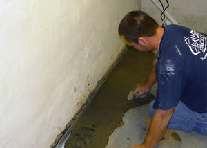 Restoring a concrete slab floor with fresh concrete after jackhammering it and installing a drain system in Woodbridge.